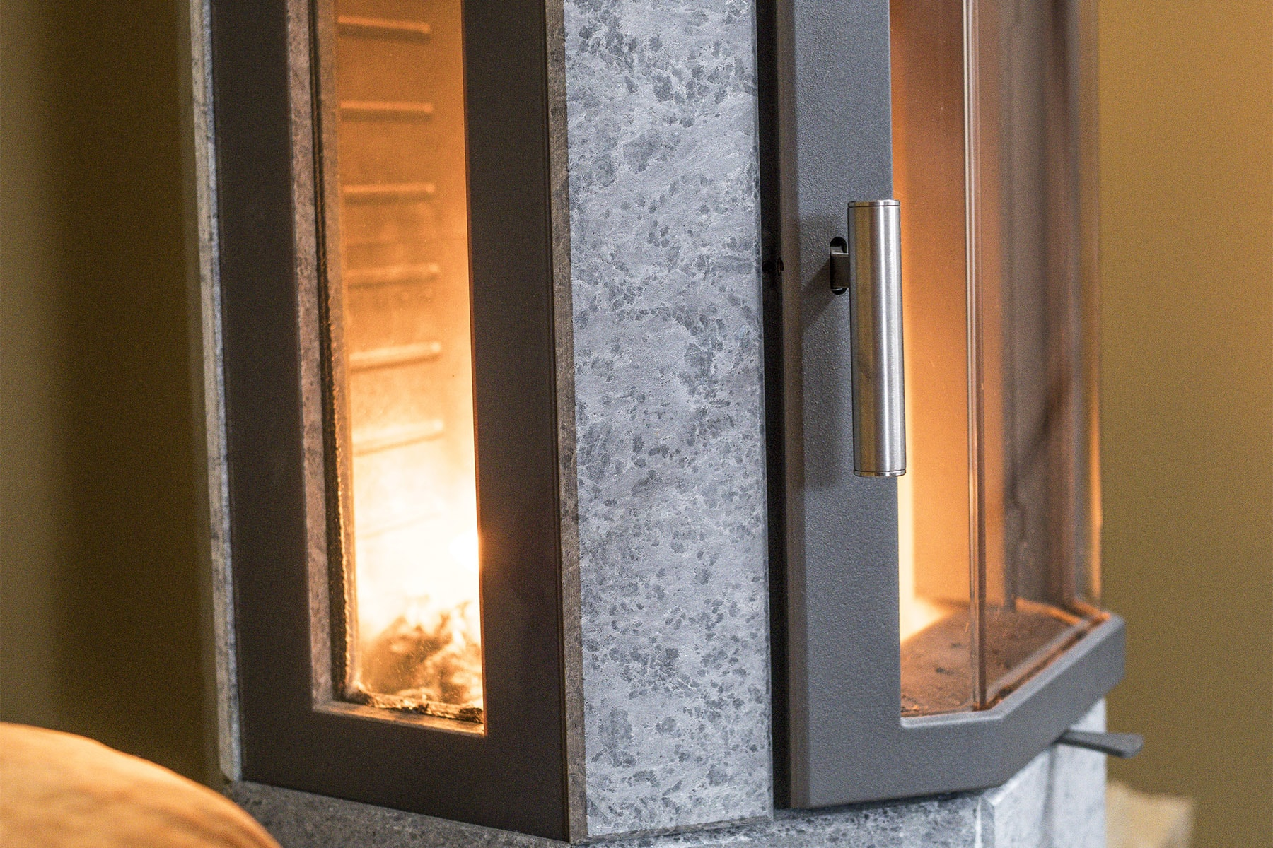 The side windows are an attractive design feature. They are elegantly pulled back one centimetre and then meshed directly into the stone without the need for a metal frame. This gives the stove a stylish and high-quality appearance.
